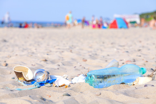 Garbage on a beach left by tourist at sunset, environmental pollution concept picture, baltic Sea coast, Dziwnowek in Poland.